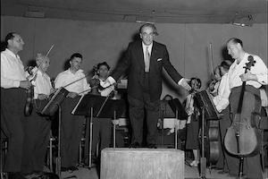 Man in tuxedo stands on podium surrounded by orchestra members holding instruments