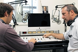 Professor Smith sits at an audio mixing board with senior Sam Lichtman in the new WVAU studio.