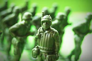 A toy soldier stands in front of other toy soldier.