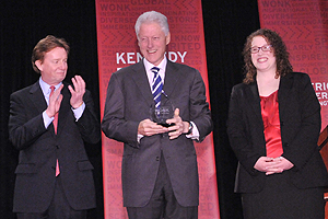President Bill Clinton accepts the Wonk of the Year award from President Neil Kerwin and Alex Kreger, student director of the Kennedy Political Union.