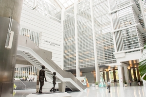 Wide view of the bright and high-ceilinged lobby of the World Bank headquarters. In the foreground is a bronze statue of a child and adult.