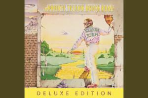 Album art from Elton John album Goodbye Yellow Brick Road. Man walking through a brick doorway onto the yellow brick road from Wizard of Oz.