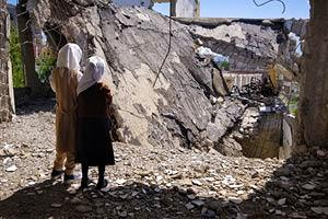 Schoolchildren stand on their destroyed school in the Yemeni city of Taiz.