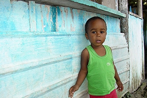 Young Brazilian child standing against a blue wall.