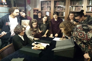 At the Walters Art Museum, Dr. Martina Bagnoli shows Dr. Allen's Medieval Art History class a bound manuscript.