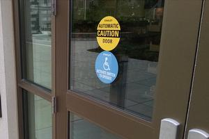 An automatic door on campus. Stickers on the door read, 'Automatic Door, Caution,' and 'Activate Switch to Operate.'