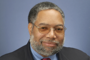 Portrait of alumnus Lonnie Bunch against blue background.