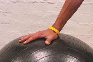 One hand resting on gray stability ball