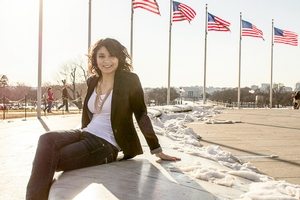 Meg Cusik poses in business attire on a snow-covered bench with several flag poles in the background.
