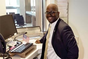 Jack Bisase smiles as he works at a computer to process immigration visas.