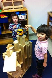 Girls playing making a tower out of blocks