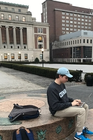 A young man sits outdoors with a laptop