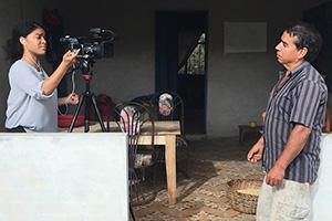 Camila DeChalus filming a Colombian farmer.