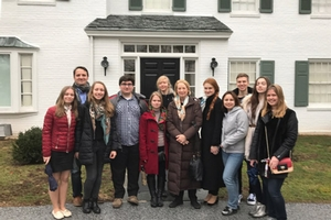Students and professors pose for a group photo outside a house.