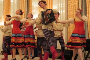 Young people in traditional costume dance and play the accordion onstage.
