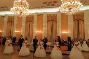 Women in white dresses with red sashes stand in an elegant ballroom with their partners.