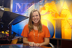 Casey Pallenik, '08, sits behind the news desk on the set of The NewsHour with Jim Lehrer