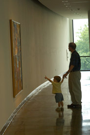 A young patron with his dad admires the artwork at the museum.