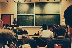 Students facing a chalkboard with equations on it and a professor standing next to it, teaching
