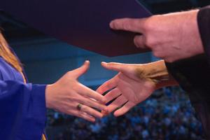 A Student shakes hands with AU President Neil Kerwin at a 2010 commencement ceremony.