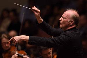 Conductor leads orchestra using baton