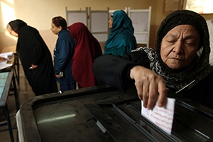Veiled women casting ballots for a vote.