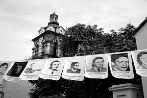 Flyers with photos of disappeared young people are hung in front of a church
