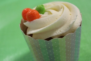 A cupcake with vanilla frosting and berries.