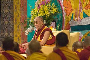 The Dalai Lama in front of a painted religious banner conducts a teaching at American University