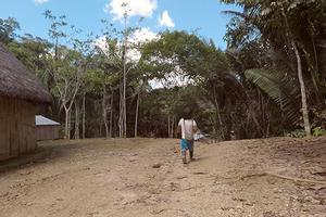 Indigenous person walking through rainforest