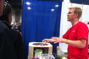 Director of Physics Laboratories Jonathan Newport teaches booth visitors about ooblecks.