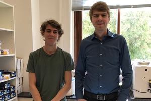Two young men stand in an office. One is considerably taller