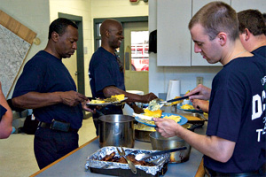 Photo: Firefighters help themselves to dinner cooked by their colleague, Danny Faison