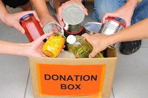 People putting food items into donation box