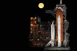 Photo: Under a nearly full moon, the space shuttle Discovery sits atop a launch pad at the Kennedy Space Center.