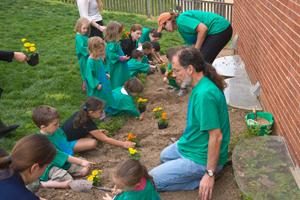 Children planting flowers during Campus Beautification Day