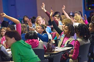 Girl Scouts raise their hands for questions at a financial literacy seminar.