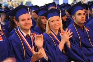 American University graduates clapping in blue caps and gowns