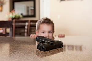 A small child staring at a hand gun within reach on a table.