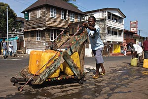 Youth haul water around Freetown, Sierra Leone, on carts built of scrap wood.