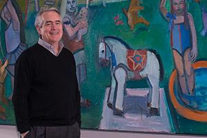 Jack Rasmussen stands smiling in front of a painting in the AU Museum.