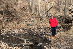 Person in a jacket stands in the woods next to a stream