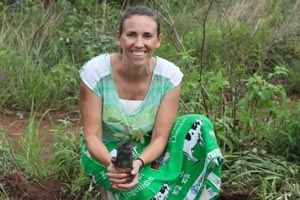 Alumna Lynn Schneider holds a sweet potato she's preparing to plant in the dirt