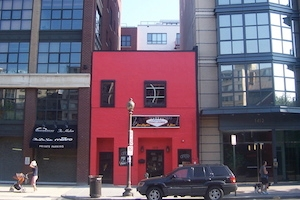 A red house is sandwiched between new development projects in Washington, D.C.