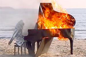 photograph of piano burning on beach