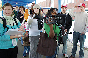 a student holds a camera while others look on