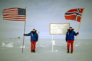 Ann Bancroft, left, and Liv Arnesen, right, hoist their U.S. and Norwegian flags at the South Pole.