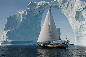 Photo of sail boat in the arctic sailing under an ice bridge.