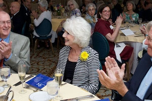 White-haired woman with a flower in her lapel sits at a table as others applaud