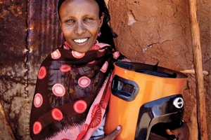 Kenyan woman holding a wood-burning stove